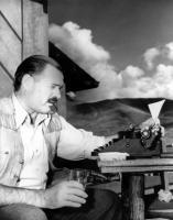Ernest Hemingway píše knihu Komu zvoní hrana - s jednou rukou na stroji, druhou na skleničce